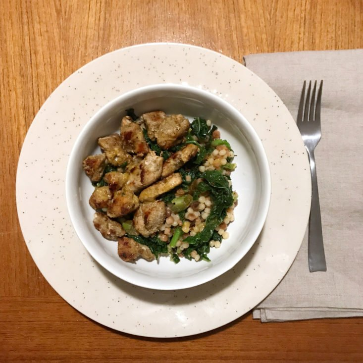 Plated Tuscan-spiced chicken and fregola sarda with warm citrus vinaigrette