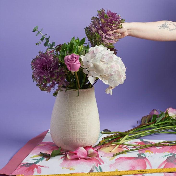 adding flowers to vase