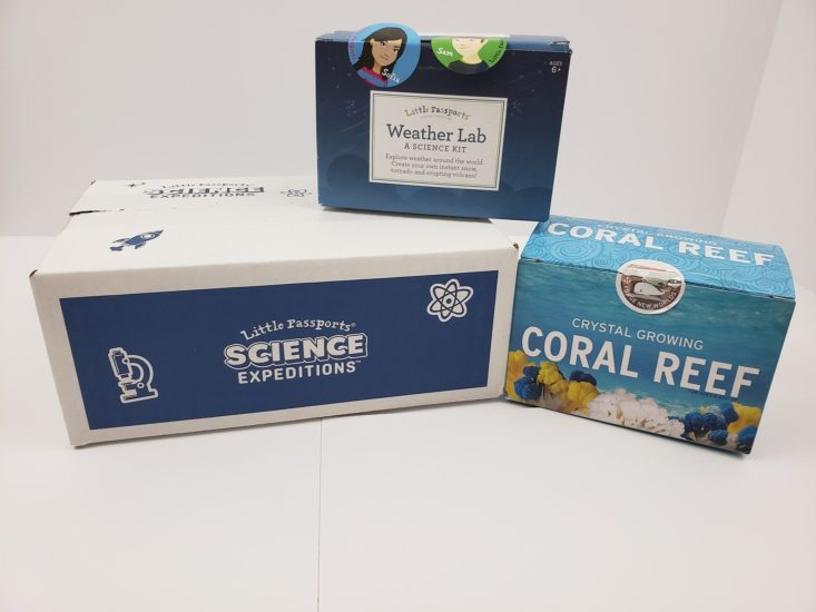Little Passports science expeditions box with weather lab kit and crystal growing coral reef kit.