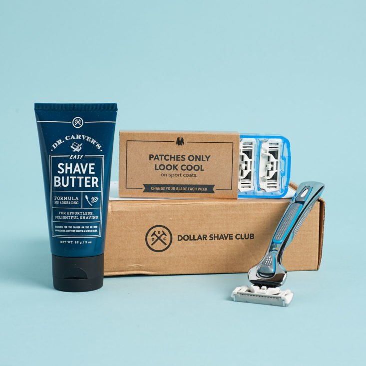 Dollar Shave Club box with razor, refill blades, and shave butter on display.